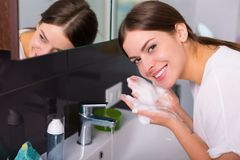 Woman washing up in the morning. Woman washing up her face with foam cleanser in the morning Stock Photos