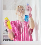 Woman washing the window glass Stock Photos