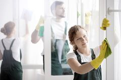 Woman washing window`s frame. A smiling women in yellow gloves washing a window frame with coworkers royalty free stock photo