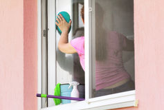 Woman washing the window. Woman washing  the window sitting on windowsill Royalty Free Stock Images