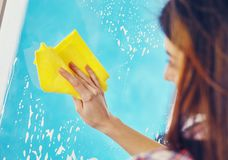 Woman Washing the Window with spray and rag Stock Photography