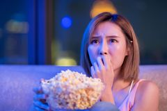 Woman watch horror movies. Young woman watch horror movies with popcorn at night stock images