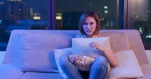 Woman watch horror movies. Young woman watch horror movies with popcorn at night stock photos