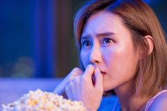 Woman watch horror movies. Young woman watch horror movies with popcorn at night royalty free stock photography