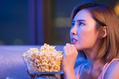 Woman watch horror movies. Young woman watch horror movies with popcorn at night royalty free stock images