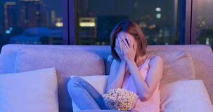Woman watch horror movies. Young woman watch horror movies with popcorn at night royalty free stock image