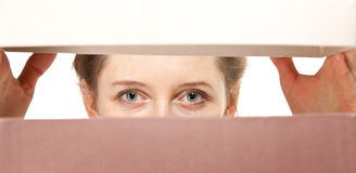 Woman watch somebody through a chink. Closeup of young woman's eyes watching you closely Stock Images
