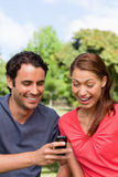 Woman watches as she is shown something on the friend's phone Stock Photography
