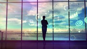 A woman watches charts and data of business processes. In the large office opposite the panoramic window stands the silhouette of the business lady and studies