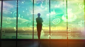 A woman watches charts and data of business processes. In the large office opposite the panoramic window stands the silhouette of the business lady and studies Royalty Free Stock Photos