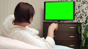Woman watches green screened TV. Dolly shot. Woman watches television with green screen / shot behind model's shoulders stock video footage