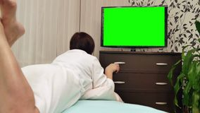 Woman watches green screened TV. Dolly shot. Woman watches television with green screen / shot behind model's shoulders stock video