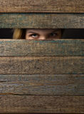Woman watches through a hole . Royalty Free Stock Photos