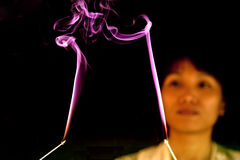 Woman watches incense smoke. Stock Photo