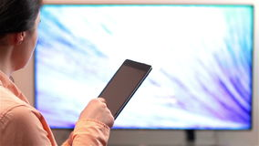Woman watches television while holding a tablet device stock video footage