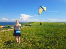 Paraglider near cliff along baltic sea coastline. Woman watching adult paraglider near cliff along baltic sea coastline and green meadow wheat field at royalty free stock photos