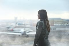 Woman watching airplanes at airport window