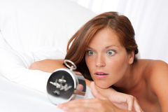 Woman watching alarm clock Stock Photography