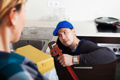 Woman watching as plumber working Stock Photos