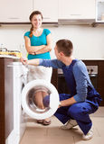 Woman watching as young  worker repairing washing machine Stock Photos