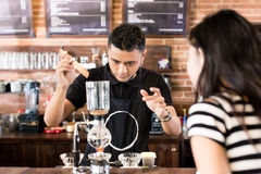Woman watching barista preparing drip coffee in cafe Royalty Free Stock Image