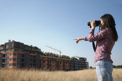 Woman watching with binoculars building Royalty Free Stock Image