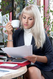 Woman watching business papers and drinking coffee Royalty Free Stock Images