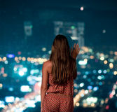 Woman watching the city at night. Woman standing back and watching the city at night through the stained-glass window Royalty Free Stock Images