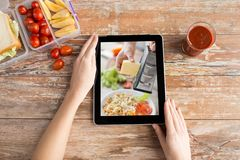 Woman watching cooking video on tablet computer stock image