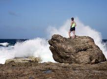 Woman watching crashing waves Stock Photos