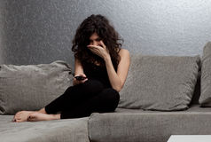 Woman watching drama on TV Stock Images