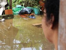 Woman watching flood in her house. Woman watching flood in her home in the favela in sao paulo Brazil stock photography