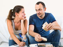 Woman watching her husband counting money Royalty Free Stock Images