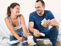 Woman watching her husband counting money Stock Photo