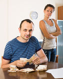 Woman watching her husband counting money Royalty Free Stock Photography