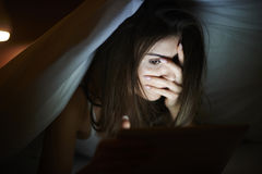 Woman watching horror movie on tablet Stock Photo