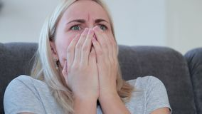 Woman watching horror movie on TV stock video footage