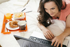 Woman watching the laptop computer and having breakfast Royalty Free Stock Photos