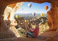 Woman watching like colorful hot air balloons flying over the valley at Cappadocia. Turkey. Volcanic mountains in Goreme national park stock photography
