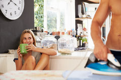 Woman Watching Man Ironing Shirt In Kitchen Stock Photo