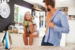 Woman Watching Man Ironing Shirt In Kitchen Royalty Free Stock Image