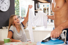 Woman Watching Man Ironing Shirt In Kitchen Royalty Free Stock Photo