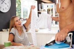 Woman Watching Man Ironing Shirt In Kitchen Royalty Free Stock Photo