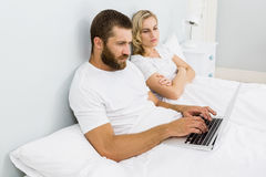 Woman watching man while using laptop in bed Stock Photo