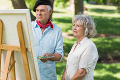 Woman watching mature man paint in park Royalty Free Stock Photography