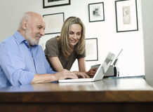Woman Watching Mature Man Use Laptop At Home Royalty Free Stock Photo