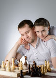 Woman watching men playing chess Stock Photography
