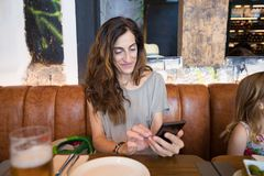 Woman watching mobile in restaurant sitting next to little girl Stock Photography
