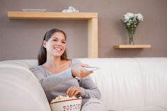 Woman watching a movie with a bowl of popcorn Stock Photos