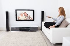 Woman watching movie on television Royalty Free Stock Photos